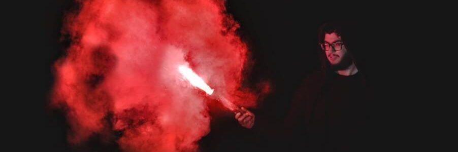 Homme avec torche a main rouge